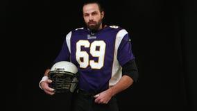 Amerikanischer Fußball Porträt eines Spielers des amerikanischen Fußballs, der einen Sturzhelm mit beiden Händen hält Ein Spieler stock video