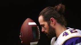 Amerikanischer Fu?ball Spieler des amerikanischen Fu?balls, der f?r das Spiel sich vorbereitet K?ssen Sie den Ball f?r amerikanis stock video