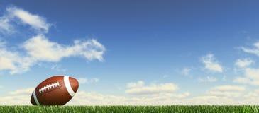 Amerikanischer Fußball, auf dem Gras, mit flaumigen Wolken am Hintergrund. Stockfotografie