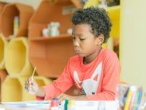 Amerikanischer Junge machen trug nach Hause Zeichnungsfarbbleistifte im Kindergartenklassenzimmer, in der Vorschulbibliothek und  Lizenzfreie Stockbilder