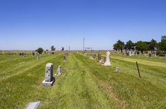 Amerikanischer Landkirchhof heraus auf den Ebenen mit einigen Gräbern verziert für Memorial Day und Ackerland im Abstand Lizenzfreie Stockbilder
