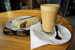 Amerikanischer Latte Kaffee der Costamarke, Frühstückssandwich und Lesebrille lizenzfreies stockfoto