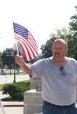 Amerikanischer Mann bewegt US-Flagge an der Sammlung wellenartig, um unsere Grenzen zu sichern Lizenzfreie Stockfotos