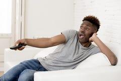 Amerikanischer Mann des attraktiven Schwarzafrikaners, der zu Hause aufpassendes Fernsehen der Sofacouch sitzt stockbilder