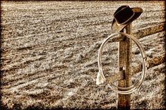 Amerikanischer Westrodeo-Cowboyhut und Lasso auf Zaun Stockfotos