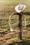 Amerikanischer Westrodeo-Cowboyhut und Lasso auf Zaun Stockbilder