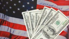 Amerikanisches Bargeld gegen einen USA-Markierungsfahnenhintergrund. Lizenzfreies Stockfoto