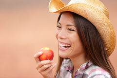 Amerikanisches Cowgirl, das Pfirsich isst Stockfotos