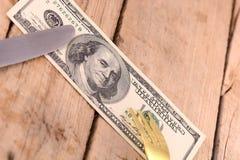 Amerikanisches Geld auf hölzerner Platte mit Messer und Gabel Stockbild