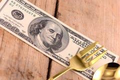 Amerikanisches Geld auf hölzerner Platte mit Messer und Gabel Lizenzfreies Stockbild