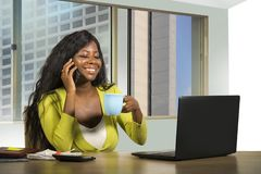 Amerikanisches Geschäftsfrauarbeiten des attraktiven Schwarzafrikaners überzeugt am Computertisch, der am Handy zufrieden gestell stockbilder