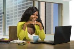 Amerikanisches Geschäftsfrauarbeiten des glücklichen und schönen Schwarzafrikaners überzeugt am Computertischlächeln zufrieden ge stockfoto