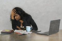 Amerikanisches Geschäftsfrauschreien des deprimierten Schwarzafrikaners traurig am Bürocomputertischgefühl besorgt und umgeben vo stockfotografie