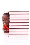 Amerikanisches kleines Mädchen des netten Schwarzafrikaners versteckt hinter einem Stapel von Stockbilder