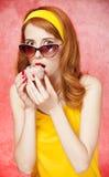 Amerikanisches Redheadmädchen in den Sonnenbrillen mit Kuchen. Stockbild