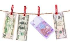 Amerikanisches und ukrainisches Bargeld trocknet auf dem Seil. Lizenzfreies Stockfoto