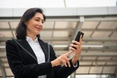 Amerikansk affärskvinna som använder smartphonen Arkivbild