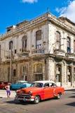 Amerikansk bil för tappning bredvid en smula gammal byggnad i havannacigarr royaltyfri fotografi