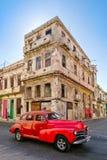 Amerikansk bil för tappning bredvid en smula gammal byggnad i havannacigarr fotografering för bildbyråer