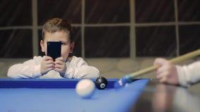 Amerikansk Billiard Pojke som spelar billiard, snooker Den lilla ungen tar fotoet lager videofilmer