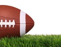 amerikansk fotboll Boll på grönt gräs som isoleras Arkivfoto