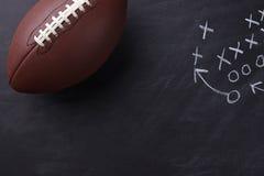 Amerikansk fotboll på den svart tavlan Arkivbild