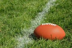 Amerikansk fotboll på naturligt gräsfält royaltyfri bild