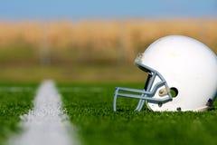 Amerikansk fotbollhjälm på fält Arkivfoto
