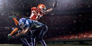 Amerikansk fotbollsspelare i handling på stadion Arkivbilder