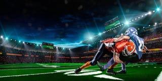 Amerikansk fotbollsspelare i handling på stadion Arkivfoton