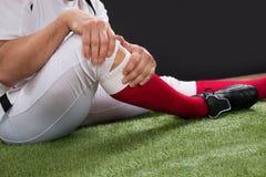 Amerikansk fotbollsspelare med skada i ben fotografering för bildbyråer