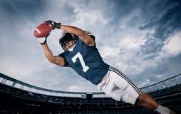 Amerikansk fotbollsspelare som fångar ett landningsögonblickpasserande Royaltyfri Foto