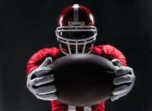 Amerikansk fotbollsspelare som poserar med bollen på svart bakgrund arkivbilder