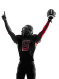 Amerikansk fotbollsspelarestående som firar landningsögonblicksilhoue Arkivbild