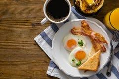 Amerikansk frukost med den soliga sidan upp ägg, bacon, rostat bröd, pannkakor, kaffe och fruktsaft Royaltyfria Foton
