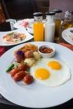 Amerikansk frukost med den stekt ägg, bacon, korven och fruktsaft Arkivbild
