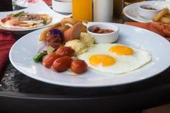 Amerikansk frukost med den stekt ägg, bacon, korven och fruktsaft Royaltyfri Foto