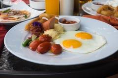 Amerikansk frukost med den stekt ägg, bacon, korven och fruktsaft Arkivfoton