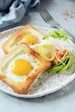 Amerikansk frukost på en platta med stekte ägg i rostat bröd, med tomater, ny daikon, morötter, arugula och espresso stekt ägg royaltyfria foton