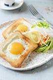 Amerikansk frukost på en platta med stekte ägg i rostat bröd, med tomater, ny daikon, morötter, arugula och espresso stekt ägg arkivbilder