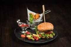 Amerikansk hamburgare på den svarta plattan, chiper, sallad, sås Royaltyfri Bild