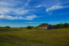 Amerikansk jordbruksmark med fältet och blå himmel med vita moln Arkivbild