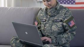 Amerikansk kvinnlig militär som skriver bärbara datorn och ler på kameran som söker information arkivfilmer