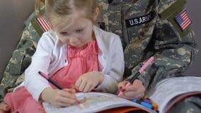 Amerikansk kvinnlig militär som tillsammans drar dottern i färgläggningboken, förälderomsorg stock video