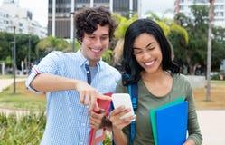 Amerikansk manlig student och indisk flicka som ser mobiltelefonen royaltyfri fotografi