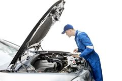 Amerikansk mekaniker som kontrollerar bilen med minnestavlan royaltyfri fotografi