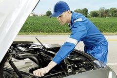 Amerikansk mekaniker som kontrollerar bilen på vägrenen arkivbilder