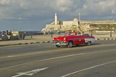 Amerikansk röd konvertibel bilkörning förbi Castillo del Morro över Havana Channel, Kuba Royaltyfria Bilder