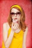 Amerikansk redheadflicka i solglasögon med caken. Arkivfoton
