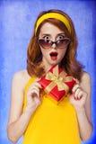 Amerikansk redheadflicka i solglasögon med gåvan. Arkivfoton